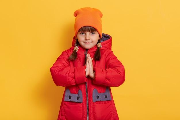 Веселая маленькая девочка, держащая руки вместе, молится и смотрит на фасад, изолированный над желтой стеной
