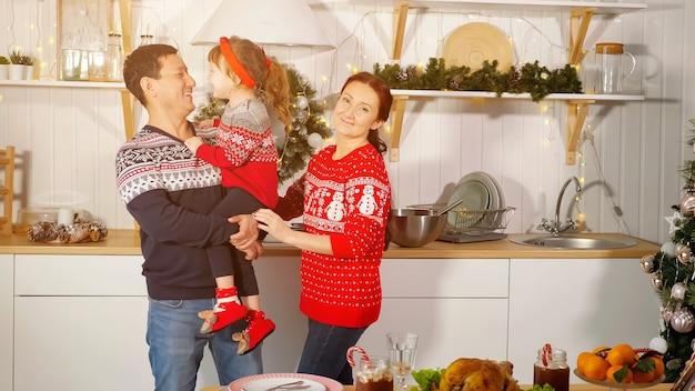 Cheerful little girl kisses smiling father making parents laugh near holiday table in kitchen