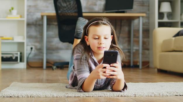 Cheerful little girl lying on the floor carpet using smartphone.