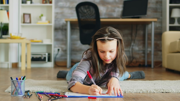 Cheerful little girl lying on the floor doing a creative drawing.