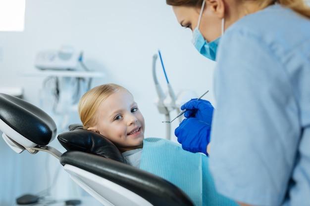 Веселая девочка лежит в кресле стоматолога и улыбается, не боясь обследования полости рта у профессионального стоматолога.