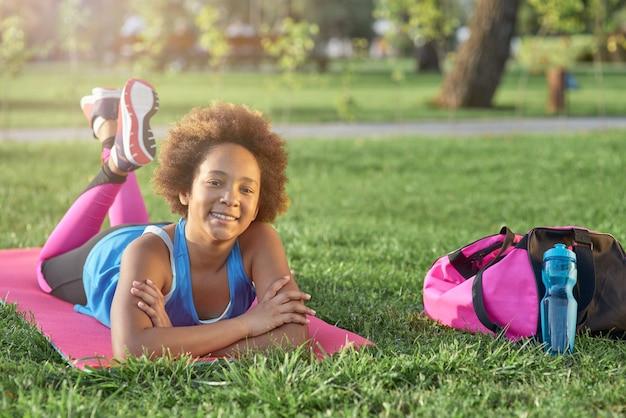 Cheerful little girl lying on yoga mat outdoors