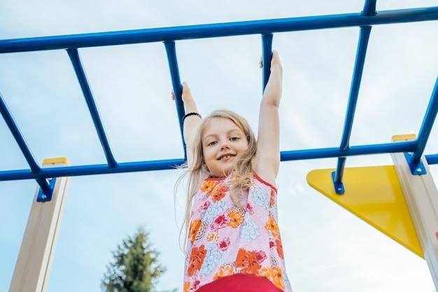 Cheerful little girl on outdoor playground equipment
