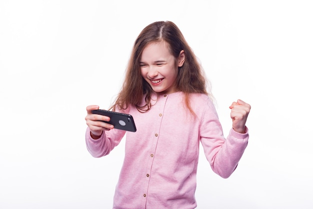 Cheerful little girl playing games at smartphone over white wall
