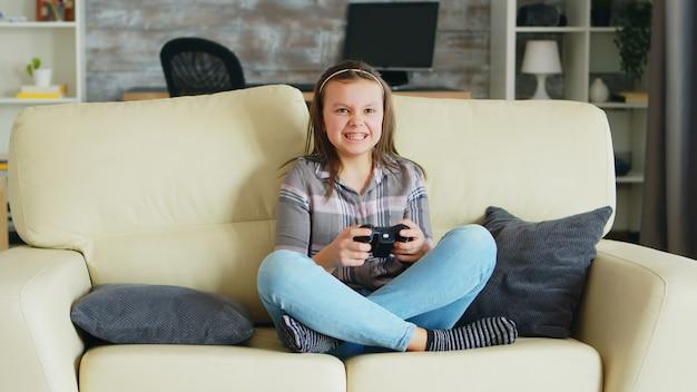 ソファに座ってワイヤレスコントローラーを使用してビデオゲームをプレイする陽気な少女。