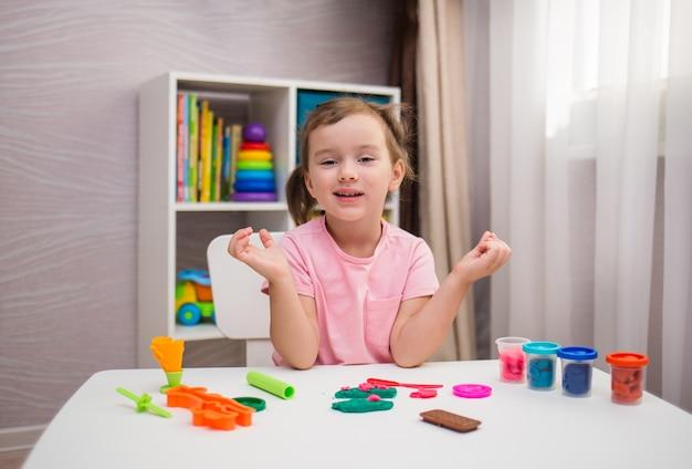 部屋のテーブルで粘土で遊んで元気な少女