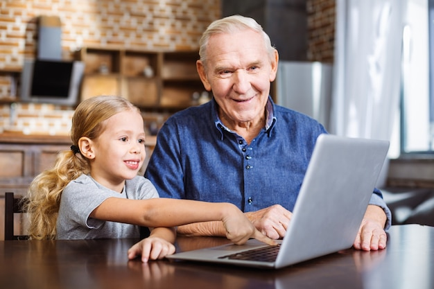 Cheerful little girl pointing the screen while using laptop with his grandfather