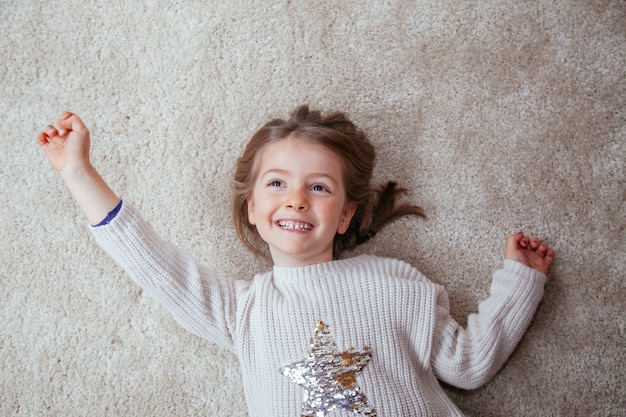 Cheerful little girl reaching for the stars