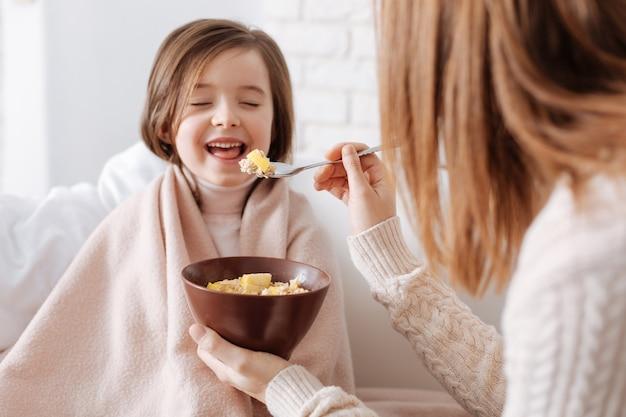 Веселая маленькая девочка сидит на диване, пока ее любящая мать завтракает