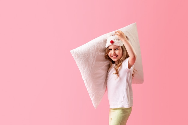 Cheerful little girl in a sleep mask with a pillow