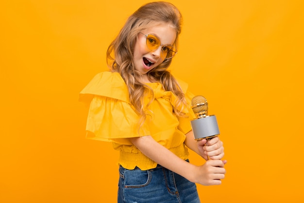 Веселая маленькая девочка улыбается на желтом фоне