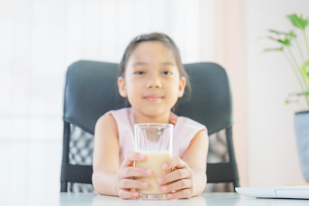 Cheerful little girl smiling and holding glass of milk