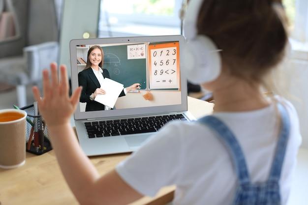 オンラインeラーニングシステムを介して勉強しているラップトップコンピューターを使用して陽気な少女