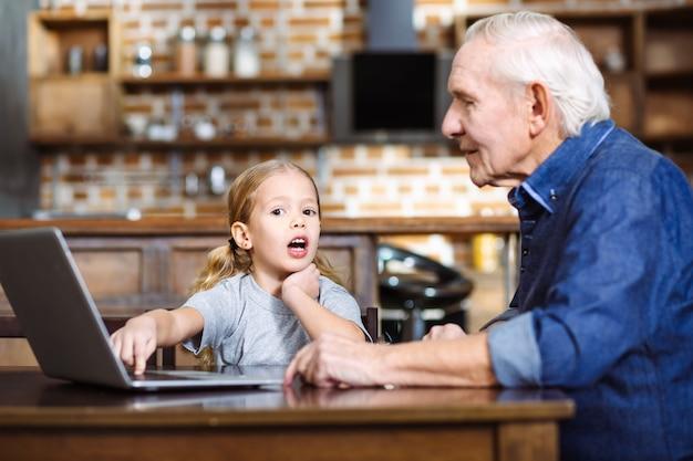 Веселая маленькая девочка с помощью ноутбука, проводя время со своим дедом