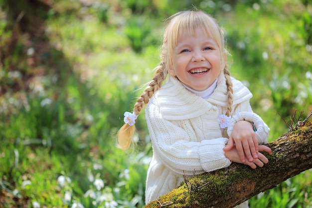 Cheerful little girl on a walk in the woods. portrait of a girl among snowdrops. bright sunny easter day