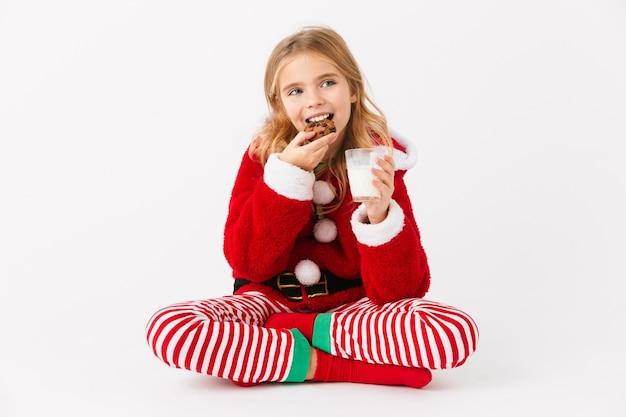 Веселая маленькая девочка в рождественском костюме сидит изолированно, ест печенье с молоком