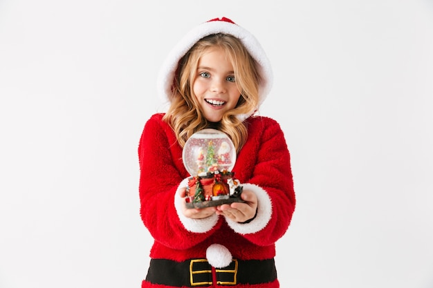 Cheerful little girl wearing christmas costume sitting isolated, holding a snow globe