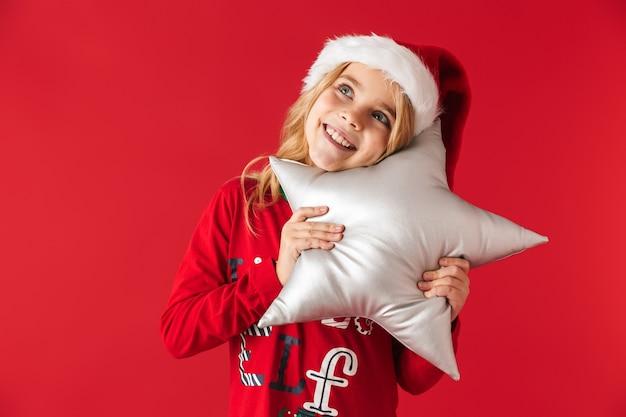 Веселая маленькая девочка в рождественском костюме стоит изолированно, держа подушку в форме звезды