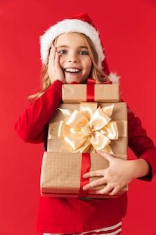 선물 상자를 들고 절연 서 크리스마스 의상을 입고 명랑 소녀