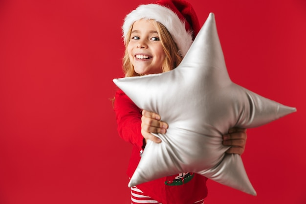 Cheerful little girl wearing christmas costume standing isolated, holding a star shaped pillow