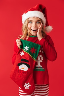 Cheerful little girl wearing christmas costume standing isolated, taking presents from a christmas sock
