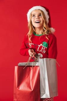 Веселая маленькая девочка в рождественской шапке стоит изолированно, неся сумки для покупок