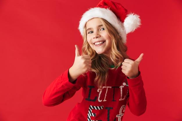 Веселая маленькая девочка в новогодней шапке стоит изолированно и показывает палец вверх