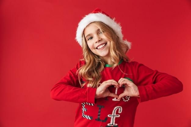 Веселая маленькая девочка в рождественской шапке стоит изолированно, показывая жест сердца