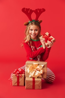 隔離されたギフトボックスのスタックと座ってクリスマストナカイの衣装を着て陽気な少女