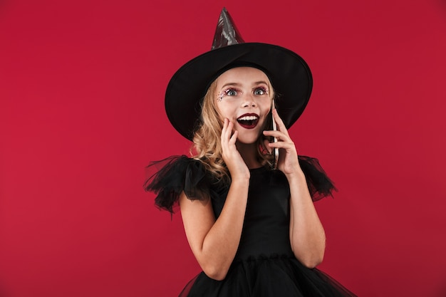 Cheerful little girl wearing halloween witch costume standing