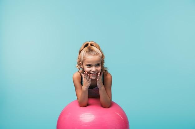 青い壁に隔離されたフィットネスボールに寄りかかってスポーツ服を着ている陽気な少女