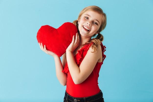 Веселая маленькая девочка в купальнике стоит изолированно над синей стеной и держит красное сердце