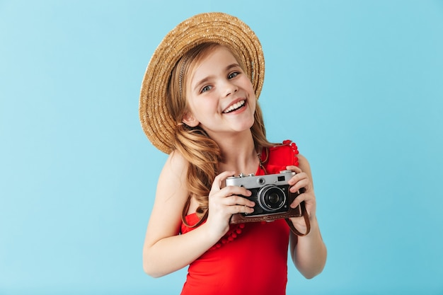 Cheerful little girl wearing swimsuit and summer hat standing isolated over blue wall, taking picture with photo camera