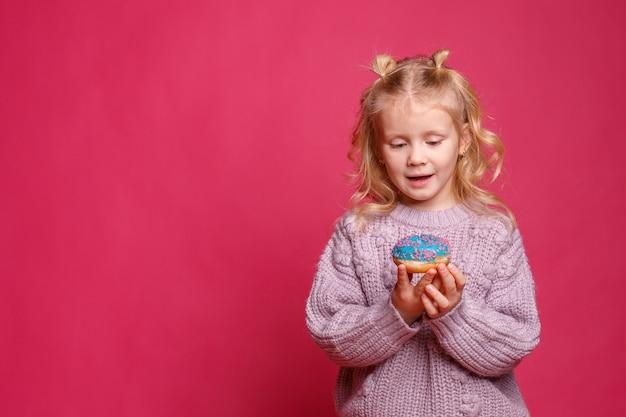 ピンクの背景にドーナツと陽気な女の子。子供は食べ物をふける。ドーナツで楽しい