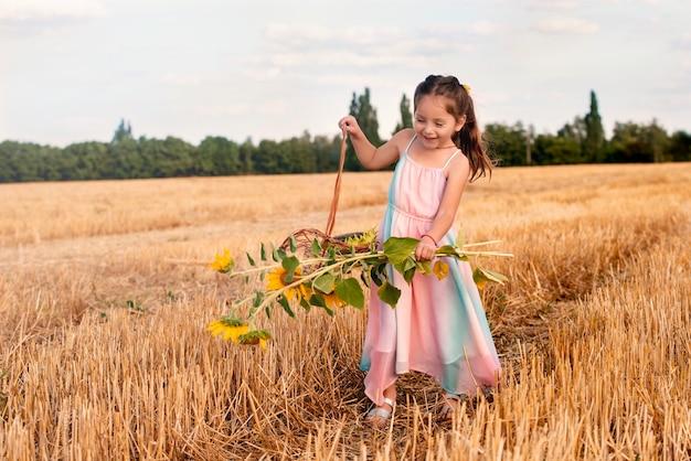 Веселая девочка с плетеной корзинкой и букетом подсолнухов в руке радостно гуляет по скошенной траве в поле теплым летним вечером. концепция времени сбора урожая