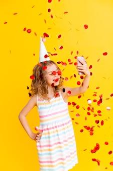 金髪の巻き毛の陽気な女の子が彼女の誕生日を祝っています。子供は携帯電話を持って、紙吹雪の雨の中で自分撮りをします。黄色の背景のクローズアップの肖像画。