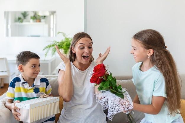 バラの花の花束を持つ陽気な少女とギフトボックスを持つ弟は、自宅で母の日に笑顔で幸せなお母さんを祝福します。母の日おめでとう!