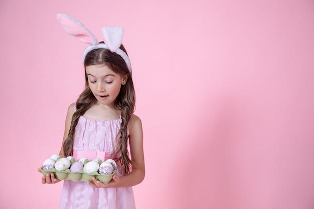 Веселая маленькая девочка с ушками пасхального кролика и подносом яиц в руках на розовом студийном фоне