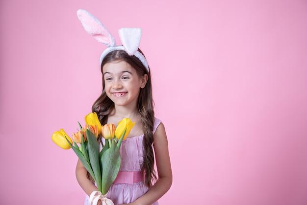 Веселая маленькая девочка с ушками пасхального кролика улыбается и держит в руках букет тюльпанов на розовом студийном фоне