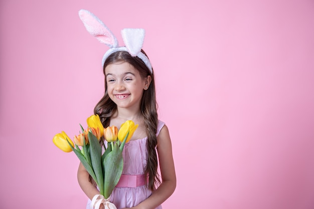 Cheerful little girl with easter bunny ears smiles and holds a bouquet of tulips in her hands on a pink studio background