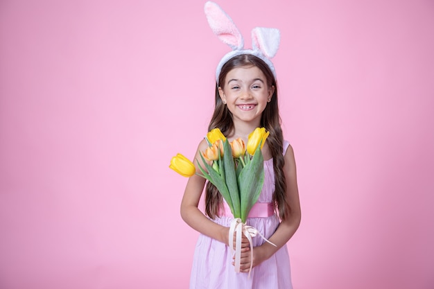 Cheerful little girl with easter bunny ears smiles and holds a bouquet of tulips in her hands on a pink wall.