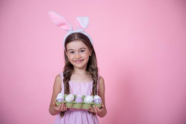 Bambina allegra con le orecchie del coniglietto di pasqua e un vassoio di uova nelle sue mani su uno studio rosa