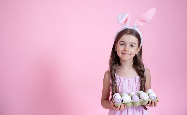 Bambina allegra con le orecchie del coniglietto di pasqua e un vassoio di uova nelle sue mani su una parete rosa. concetto di vacanza di pasqua.