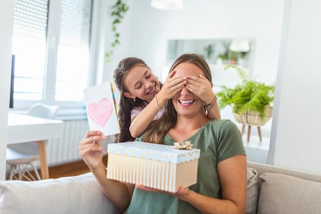 ギフトボックスとカードを持った陽気な女の子は、自宅で母の日に驚くべき幸せなママを祝福します。母の日おめでとう!