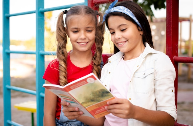 Cheerful little girls looking in a book