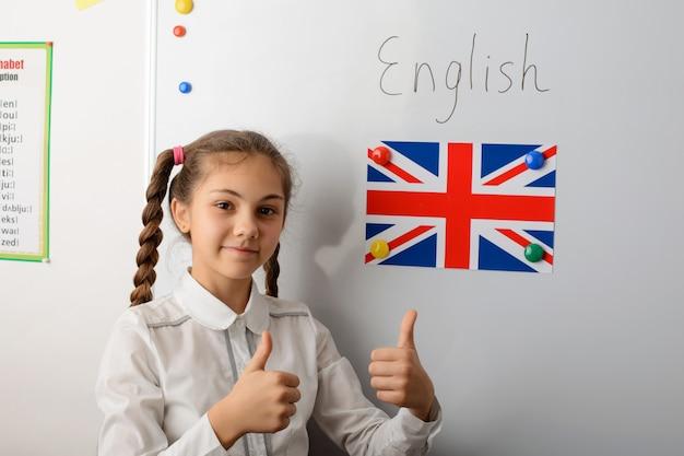 Жизнерадостный маленький европейский ученик показывая большие пальцы руки вверх