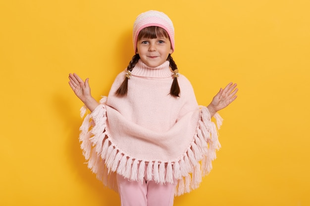 Cheerful little kid with pigtails wearing stylish poncho, cap and trousers, poses isolated on yellow wall