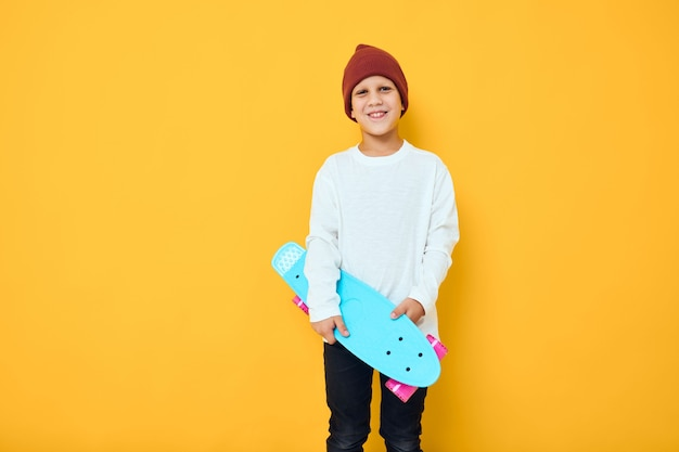 Cheerful little kid with red backpack blue skateboard isolated background