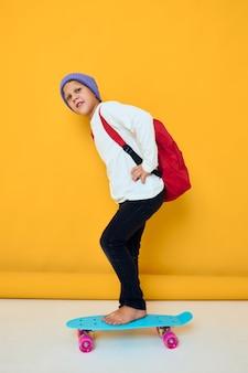 赤いバックパック青いスケートボードの孤立した背景を持つ陽気な小さな子供