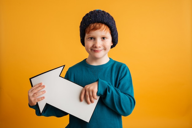 Cheerful little redhead boy holding arrow.